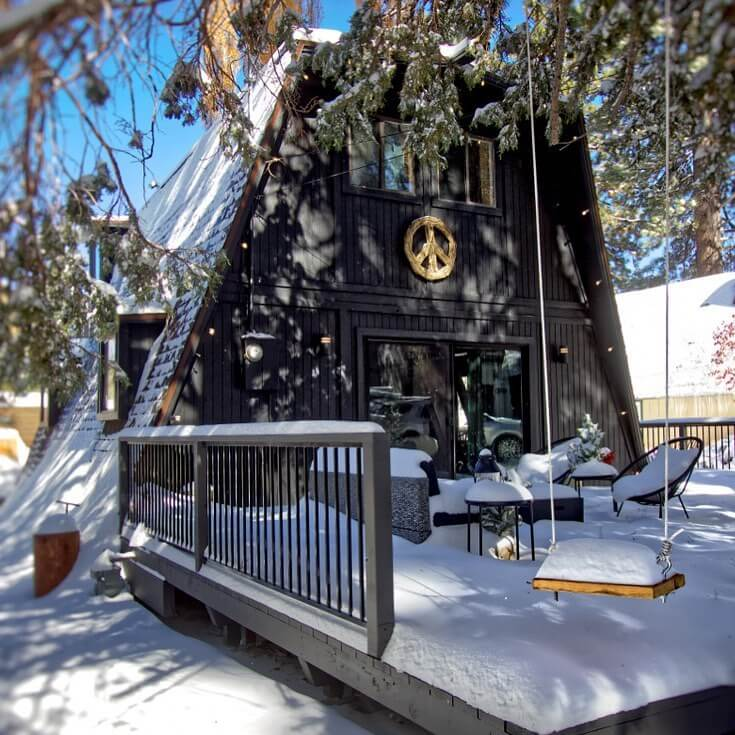 Cabin in big bear with snow on the porch and ground. Big Bear Lake is  the perfect romantic California getaway for Valentine's Day.