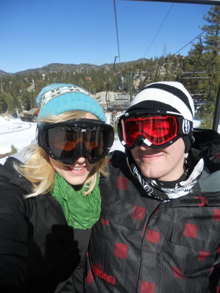 Picture of the authors, Rae and Jason sitting on a ski lift on Heavenly Mountain. Lake Tahoe is the perfect romantic California getaway for Valentine's Day.