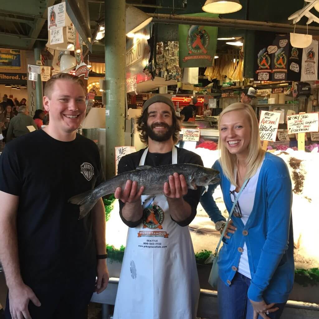 Man holding fish that was thrown to him over the counter in the Public Market in Seattle.
