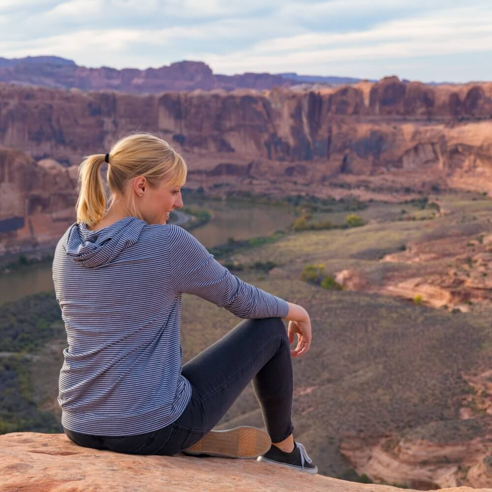 Rae Miller sitting on the edge of a cliff overlooking the Colorado River in Moab during an utv tour