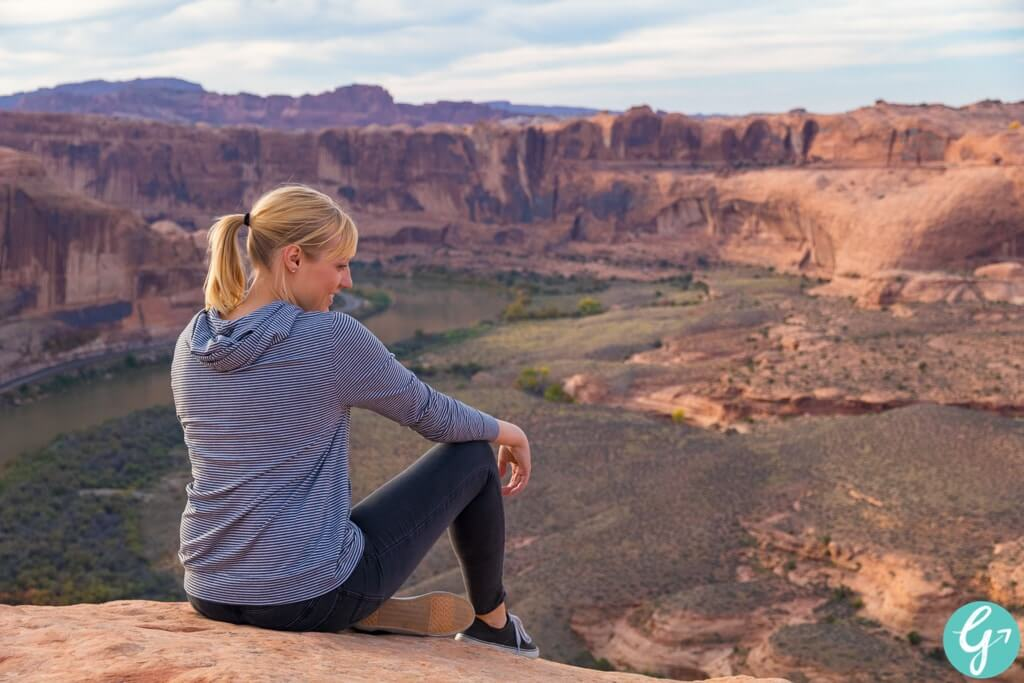 Rae Miller sits at the edge of a cliff on the Hell's Revenge Trail in Moab, UT looking at the Colorado River below.