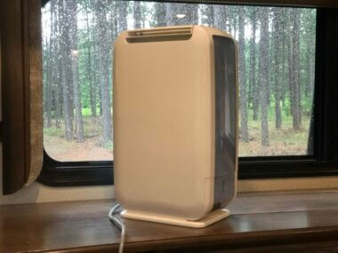 an RV dehumidifier sitting on the counter with a wet window behind it