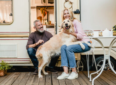 Family photo of mature couple playing with their retriever in the caravan doorway