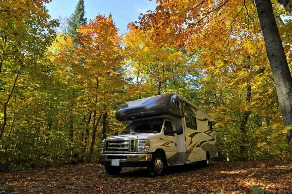 Class C RV in a campsite with fall colored leaves.