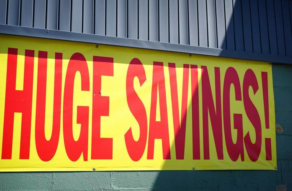 "Red and yellow sign that says ""huge savings"" at an RV dealership."