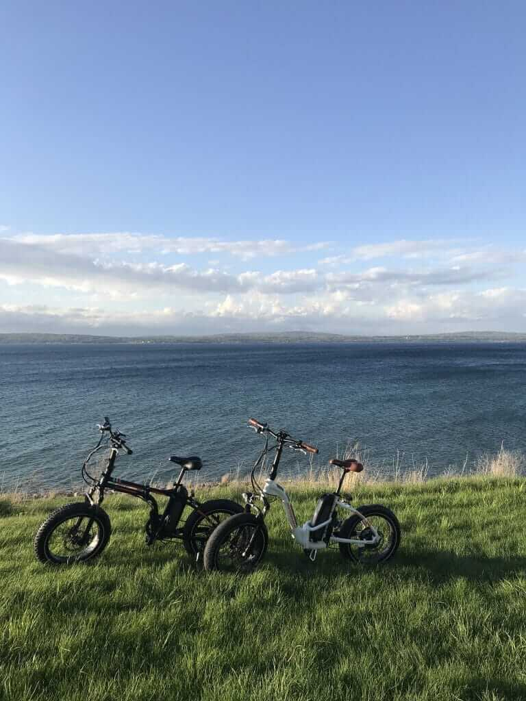 Two RadMini Electric Bicycles on the grass overlooking Lake Michigan.