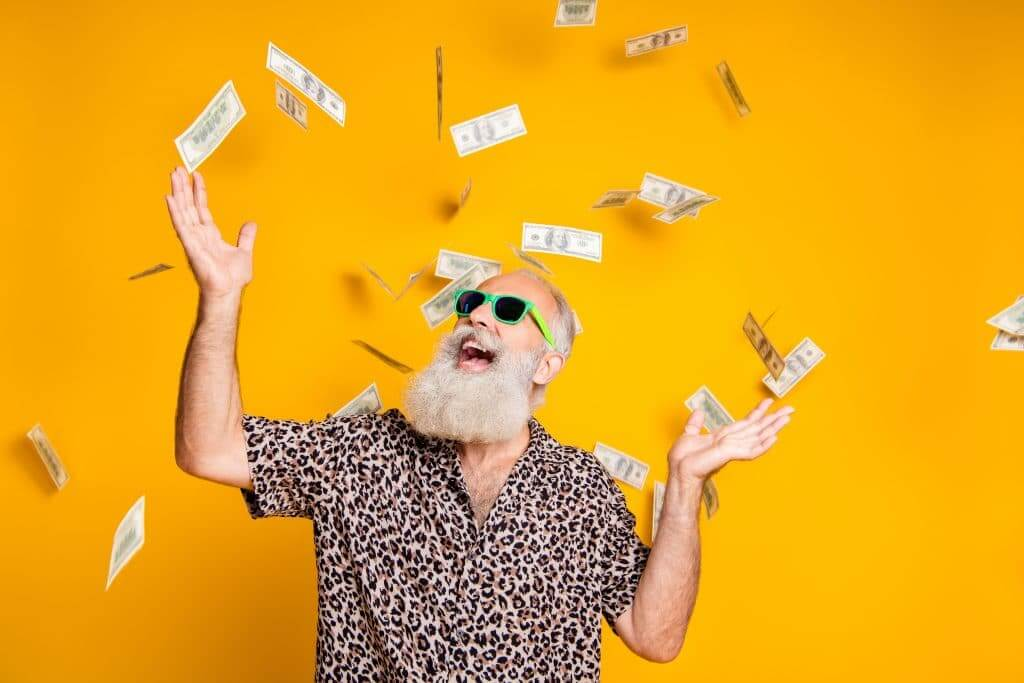 Older man with smile on his face with money falling from the sky because he saved money with Passport America.