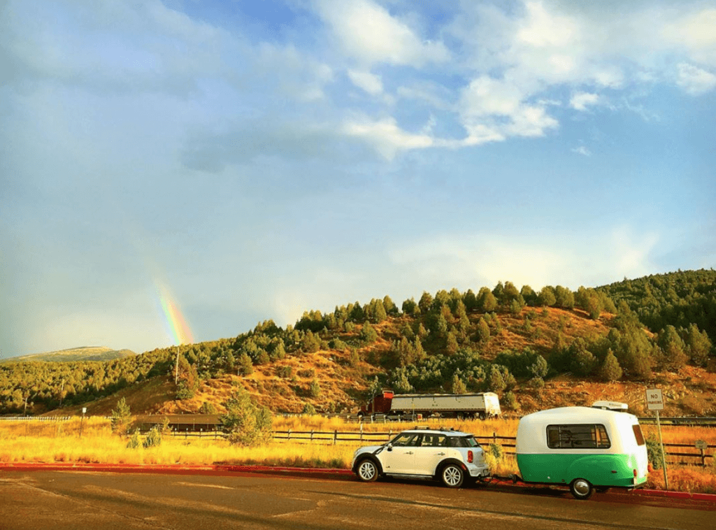 Happier Camper HC1 towed with a mini cooper sitting in a parking lot with a rainbow behind it.
