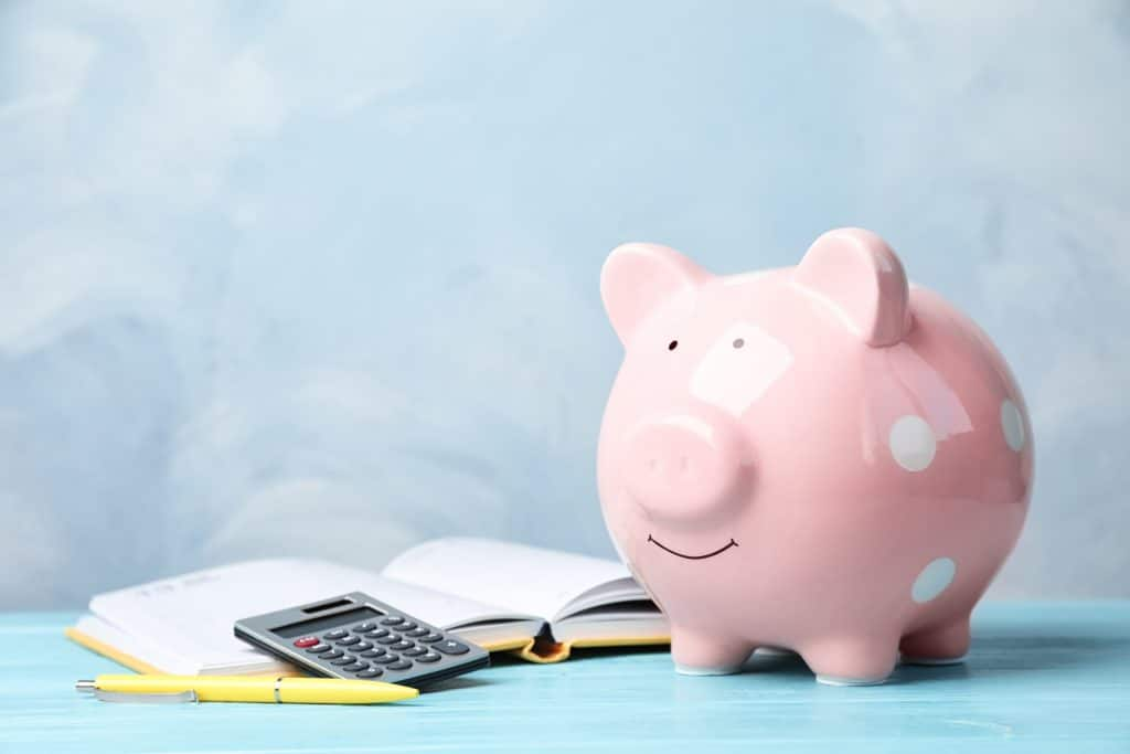 Picture of a piggy bank and book with  a pen and calculator laying on them