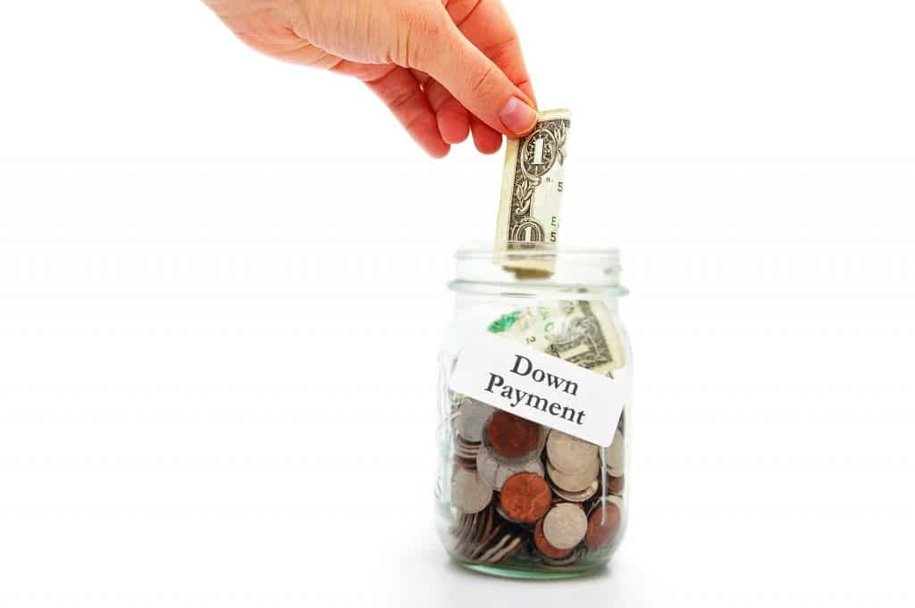 hand putting money into a down payment jar for RV loan