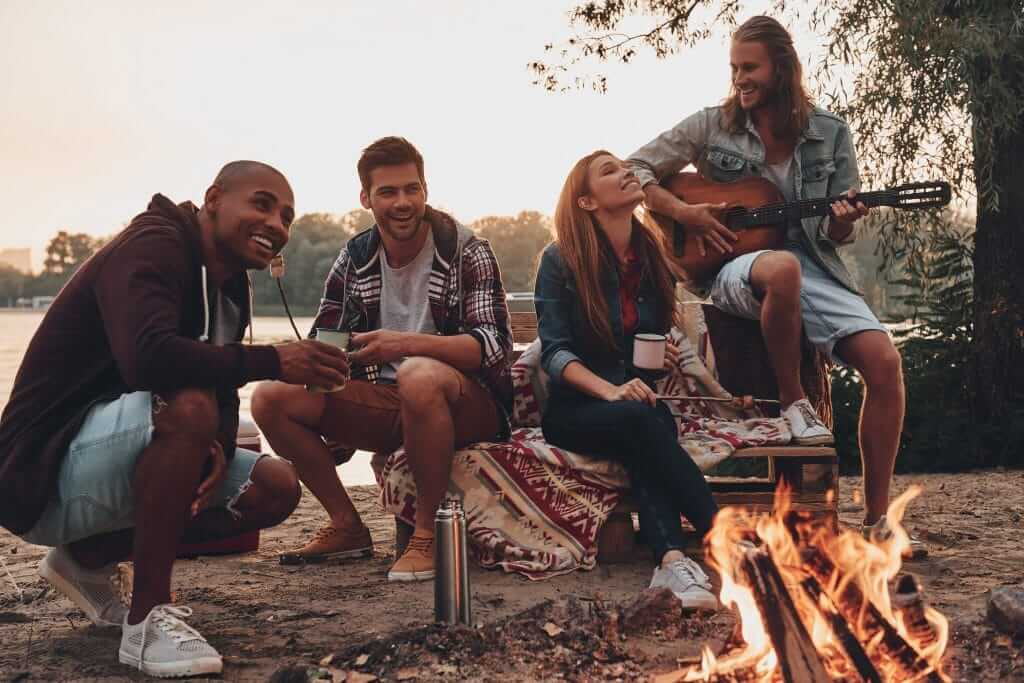 Group of young adults using their campground membership to sit around a fire on the weekend and drink coffee and play guitar.