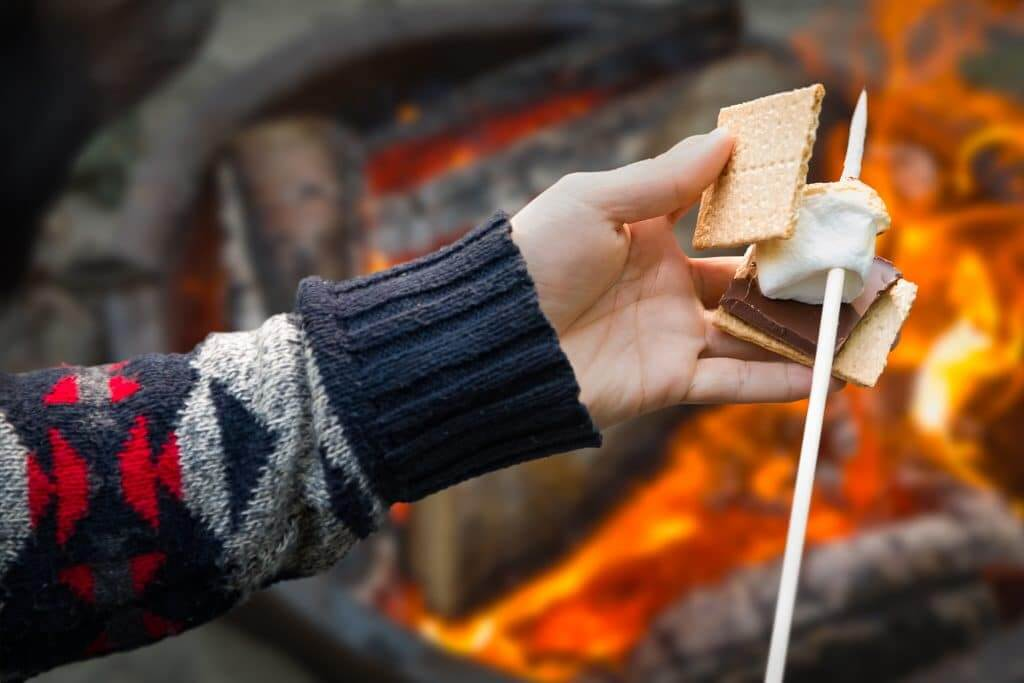 Picture of putting marshmallow on chocolate and graham cracker. Indulging can help destress in your RV.