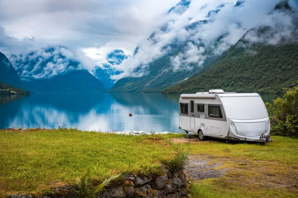 ultra lightweight travel trailer parked on amazing campsite with lake and mountains in the background