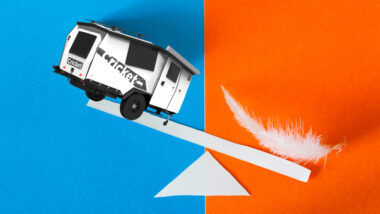 lightweight travel trailer on a scale with a feather on the otherside. The feather is showing as heavier.