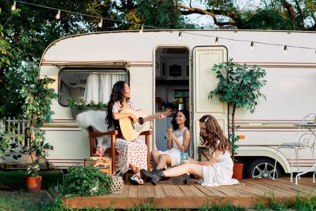 Women sitting in front an RV playing a guitar.