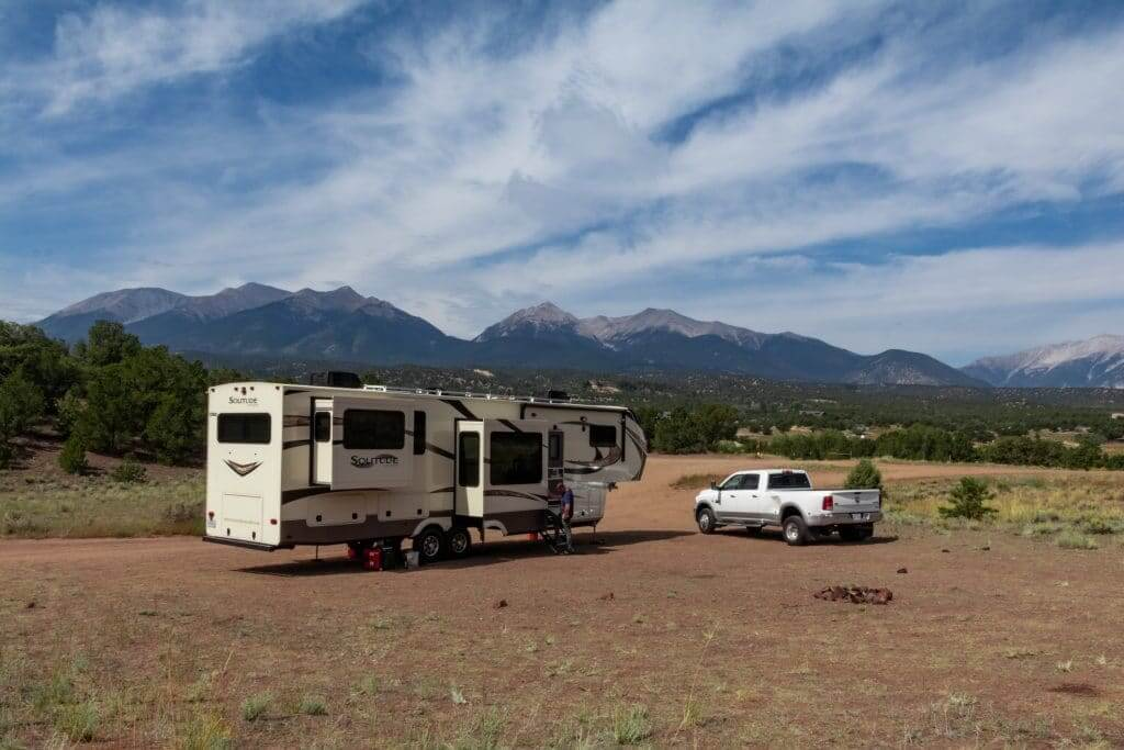 RV in a open dirt field with mountains in the background