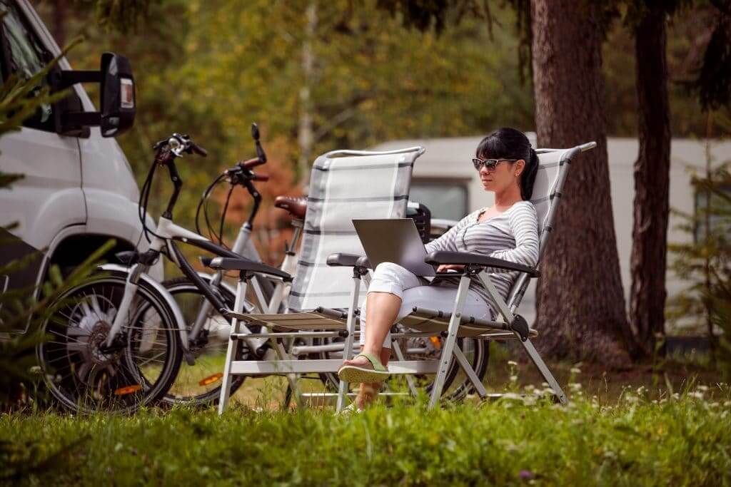Woman sitting in a chair in front of her self contained RV and two bicycles.