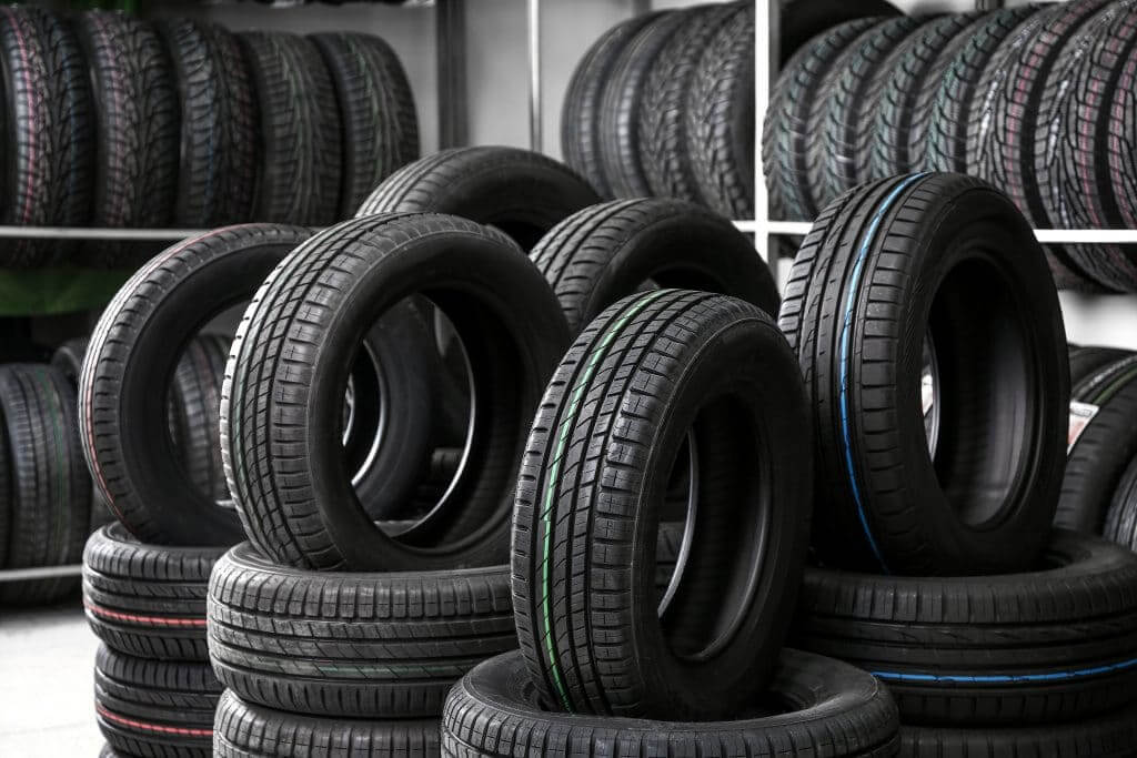 tire store with rows of tires on the wall and piles of tires on the floor