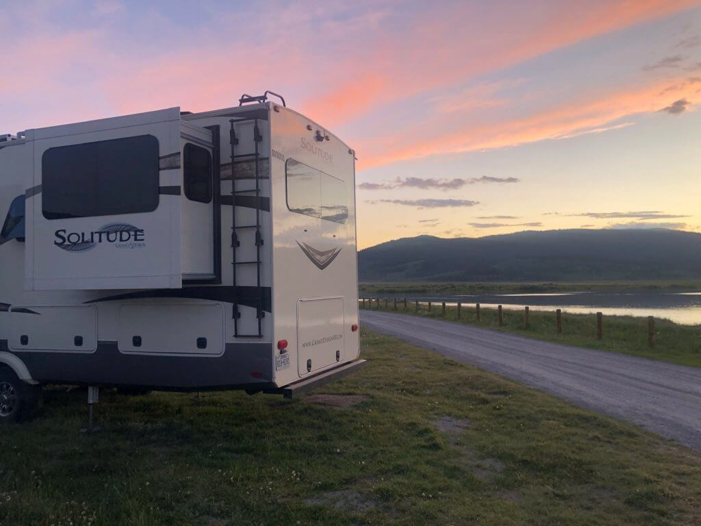 Grand Design Solitude RV is boondocking with a lake in the background