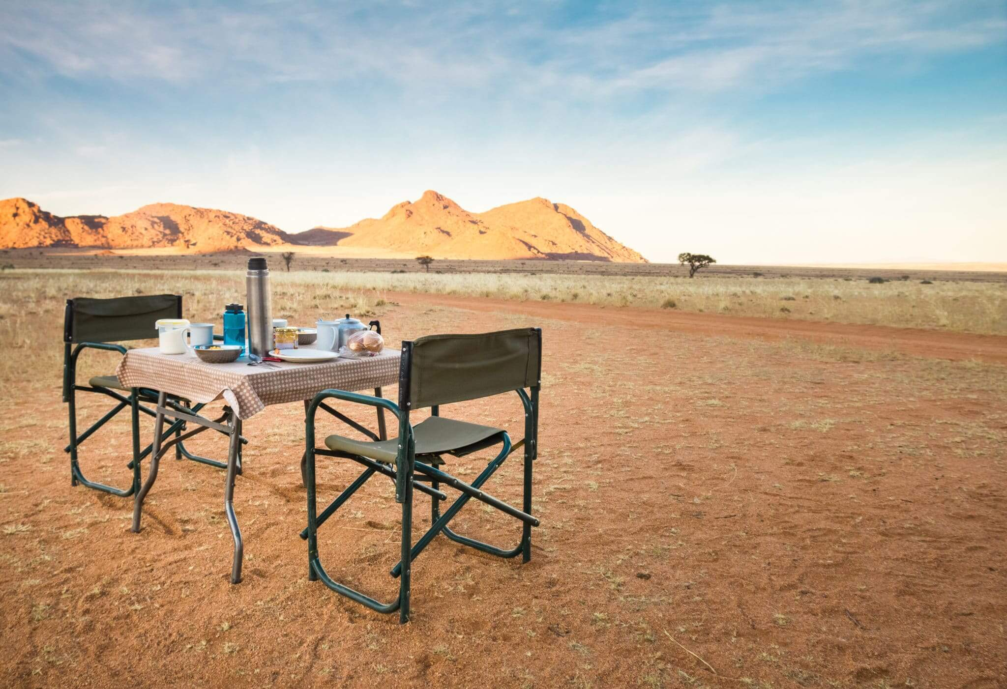Camping table and chairs in the desert at sunrise