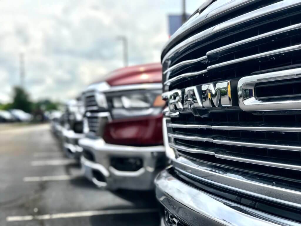 row of RAM trucks. Tow vehicle in important when comparing fifth wheel vs travel trailer