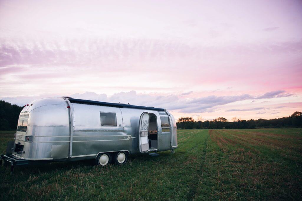Airstream travel trailer in a grass field with the front door open and purple sunset in the background