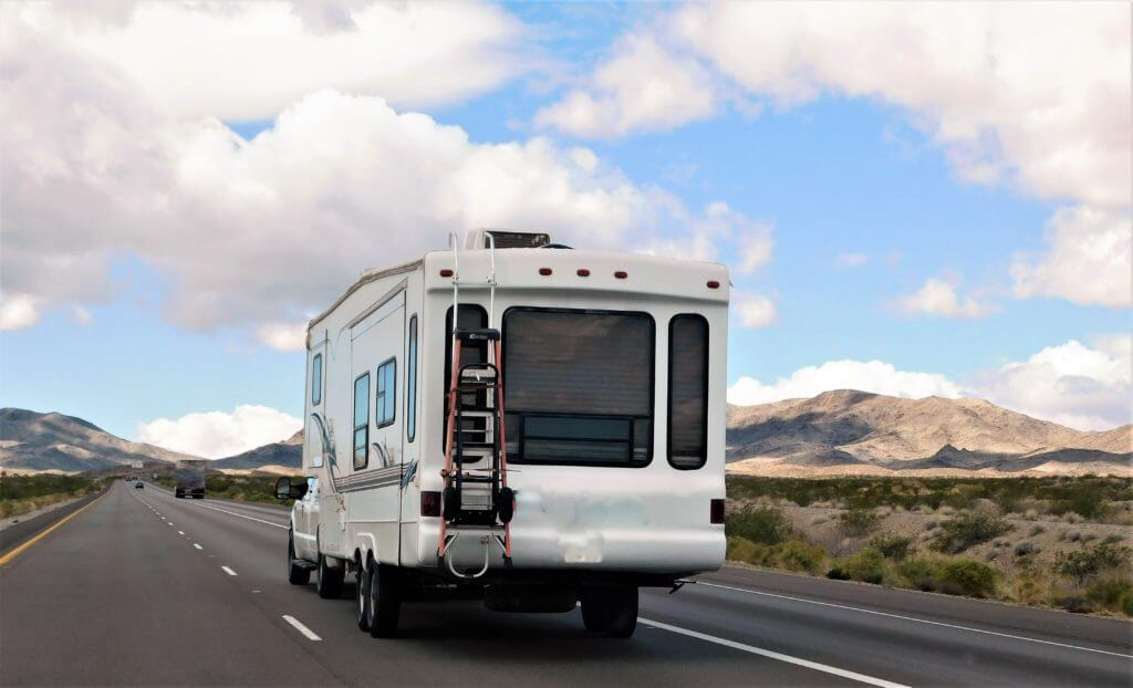 Fifth wheel being towed down the road with mountains in the background