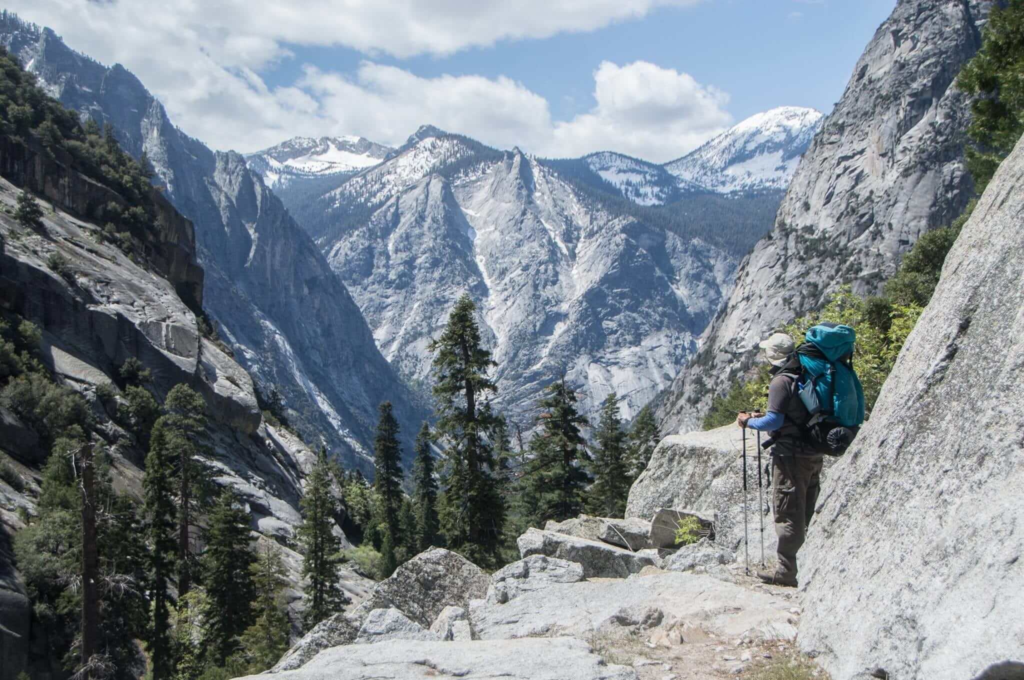 Man standing on ledge looking over Kings Canyon National park while hiking