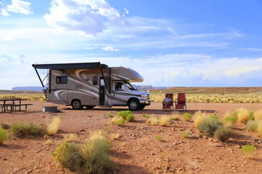 RV with the awning out boondocking on National Forest Land with two camping chairs out font