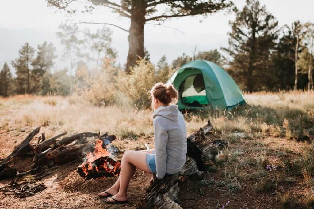 Woman sitting on stump in front of a fire and a tent respecting the rules of boondocking on national forest land