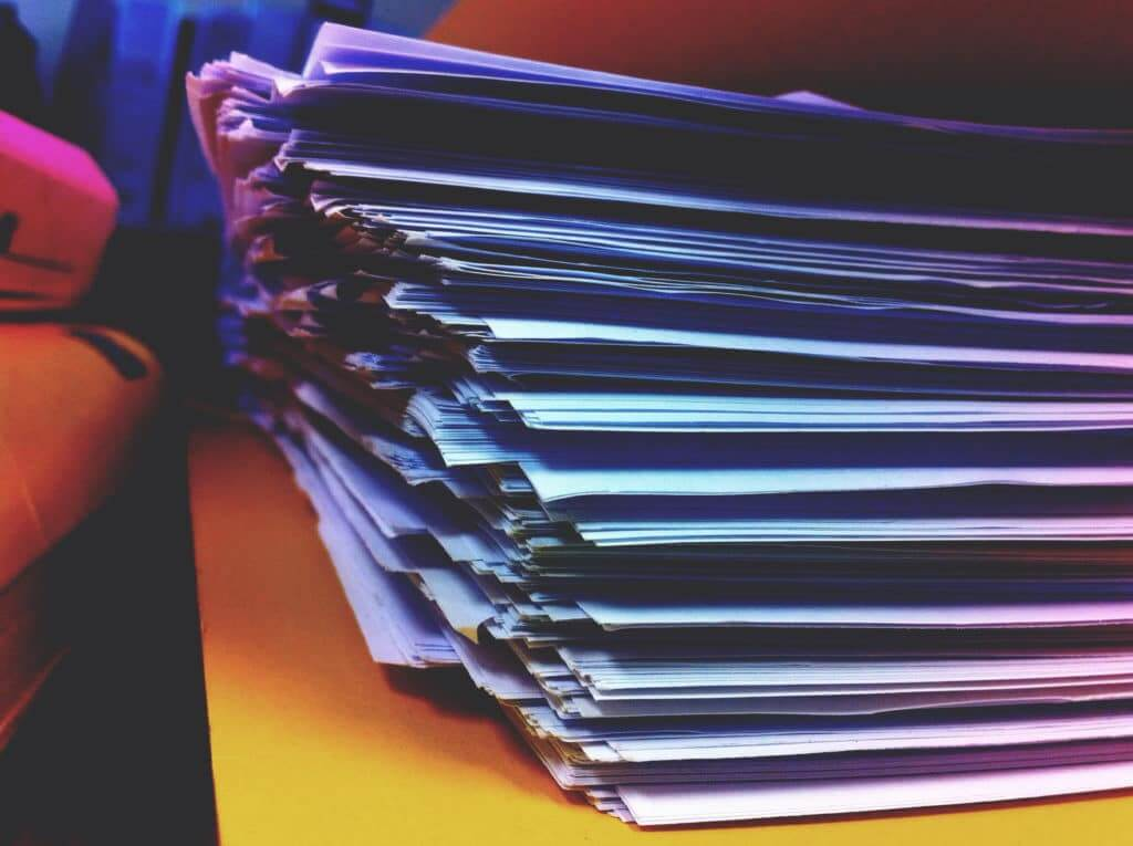 Stack of paperwork that needs to be scanned and digitized before downsizing.