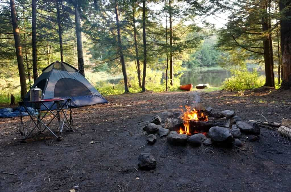 A tent with a fire burning in front. A small table with coffee on it and a beautiful lake view in the background. Staying in established campsites is a great way to abide by BLM Boondocking rules