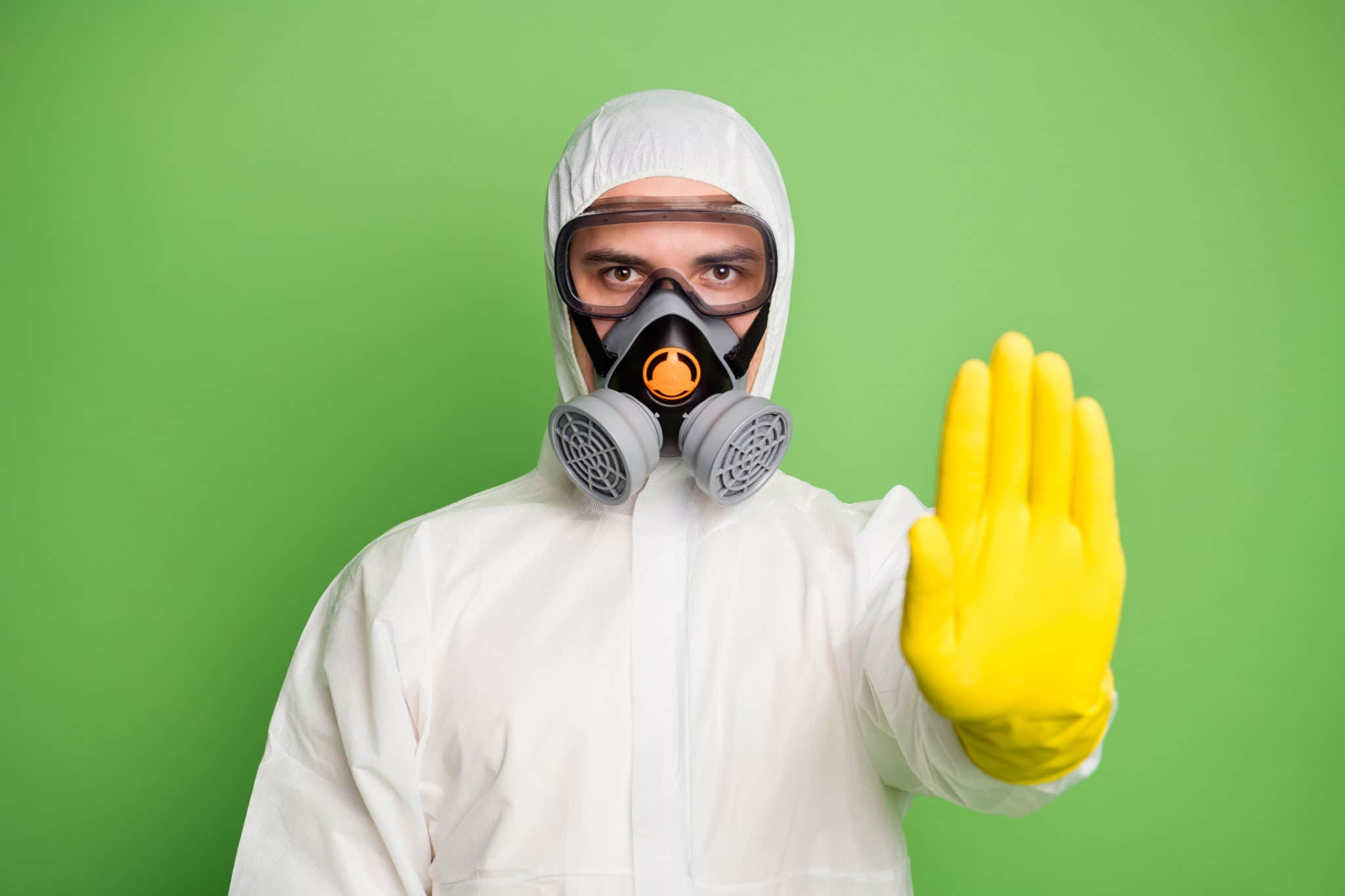 Close-up portrait of his he nice serious disinfectant workman wearing, gas mask showing palm stop sign quarantine over green pastel color background