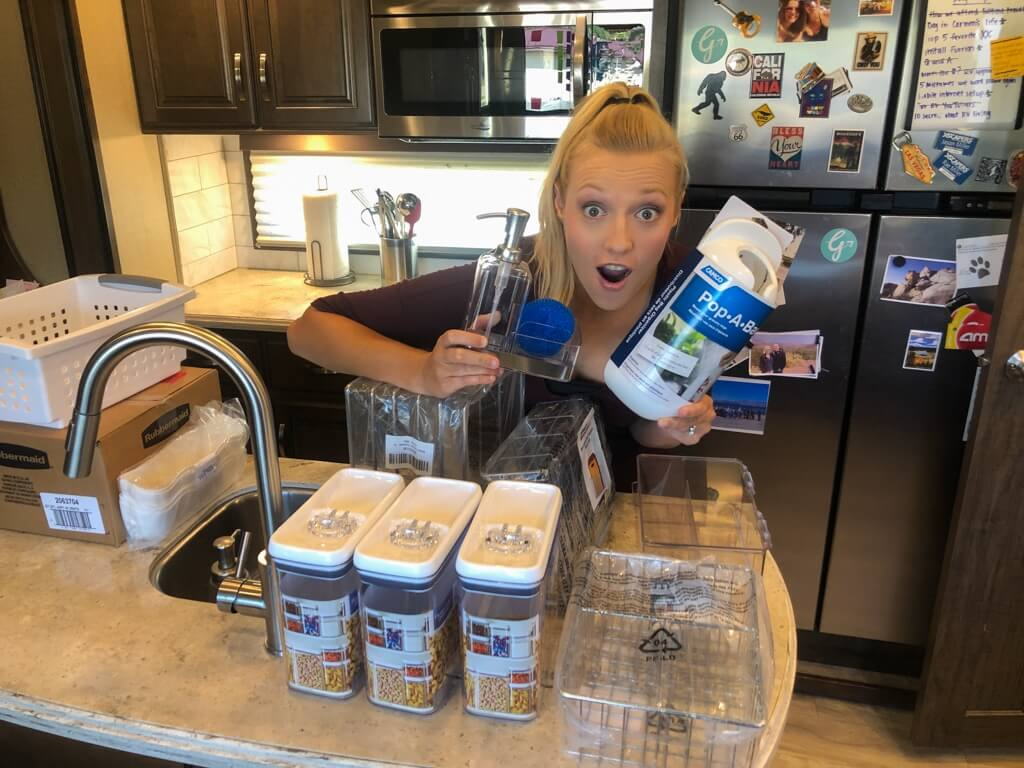 Woman holding RV kitchen accessories and looking excited