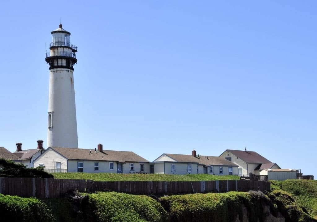 A white building and a lighthouse with clear blue skies in the background and green bushes in the foreground. This is Lighthouse Point, one of the things to do in Santa Cruz.