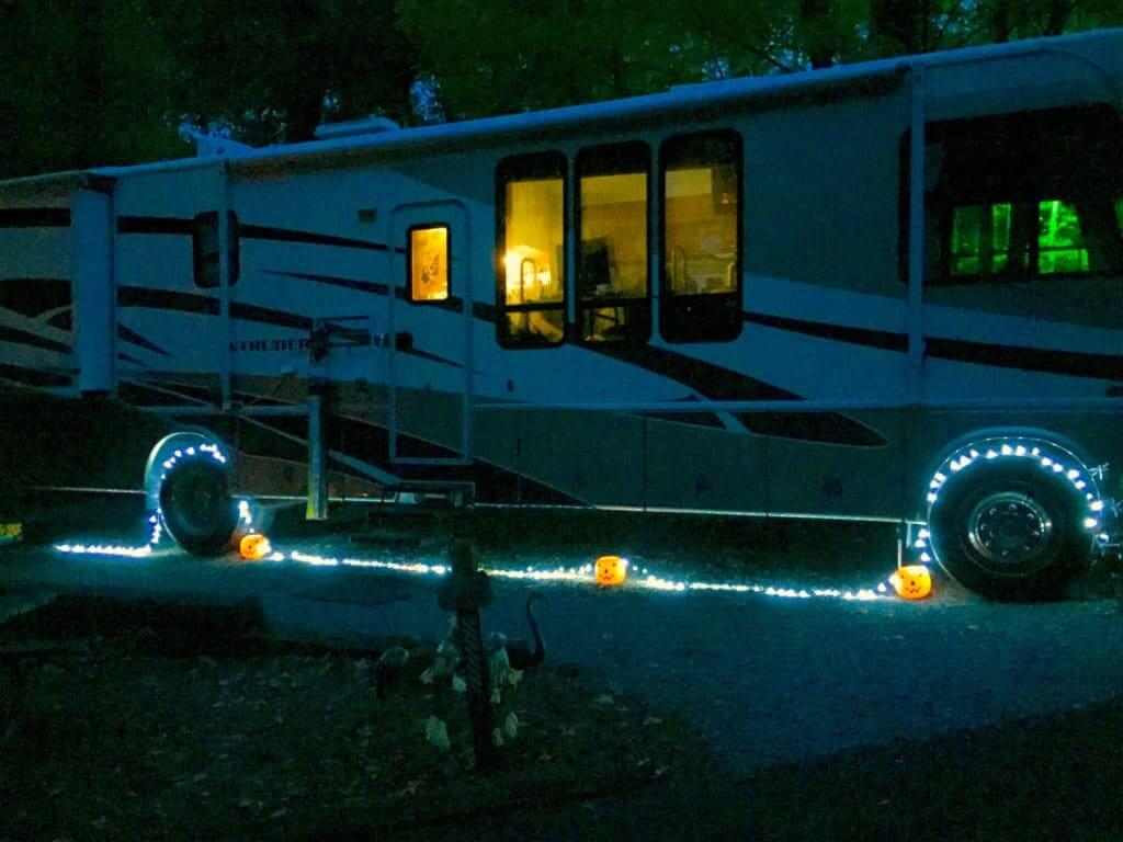 A minimal take on RV halloween decorations: a Motorhome with blue string lights and three orange lightup pumpkins.