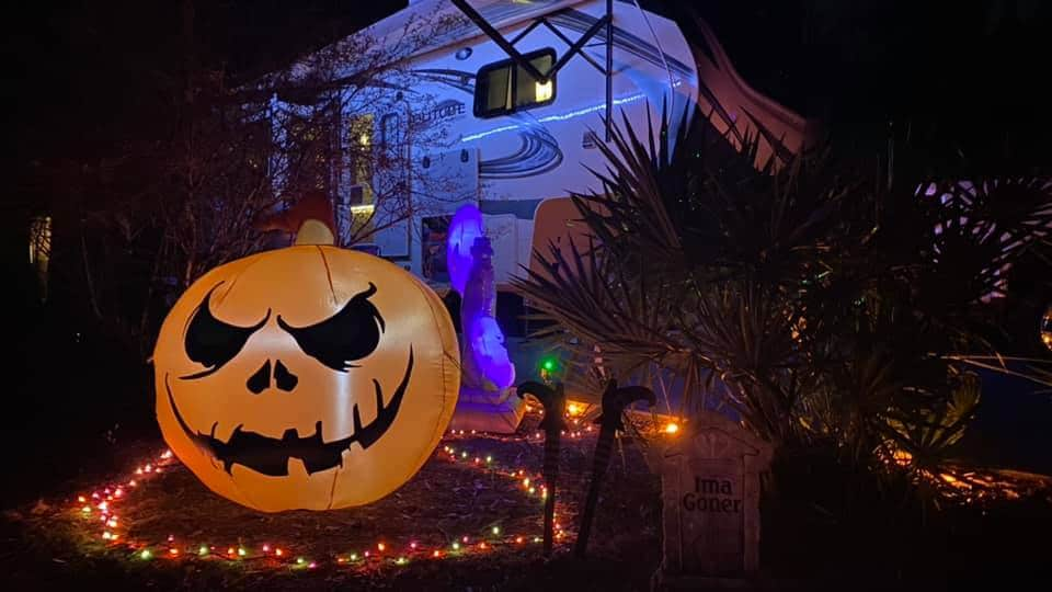 Pictured RV halloween decorations: Giant blowup carved pumpkin with orange string lights and a Grand Design Solitude RV in the backgound