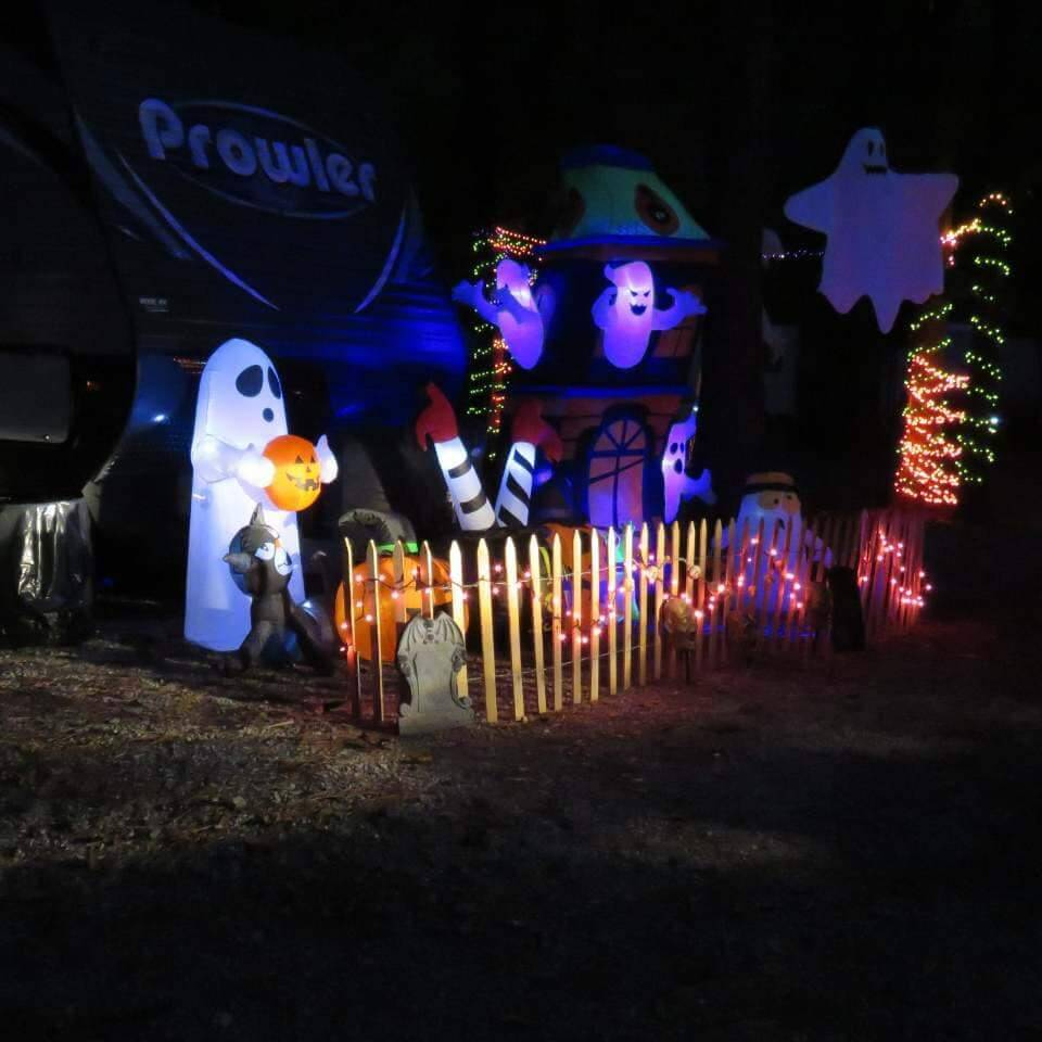 A fun take on RV halloween decorations: a Prowler travel trailer with orange string lights and a lot of blowup ghosts in the yard.