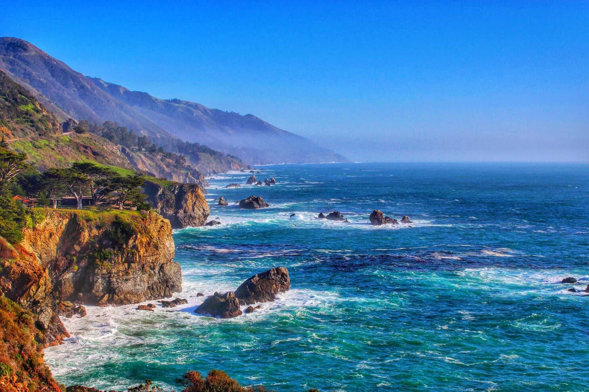 Coastal view of Big Sur with mountains and deep blue ocean crashing against the cliffs