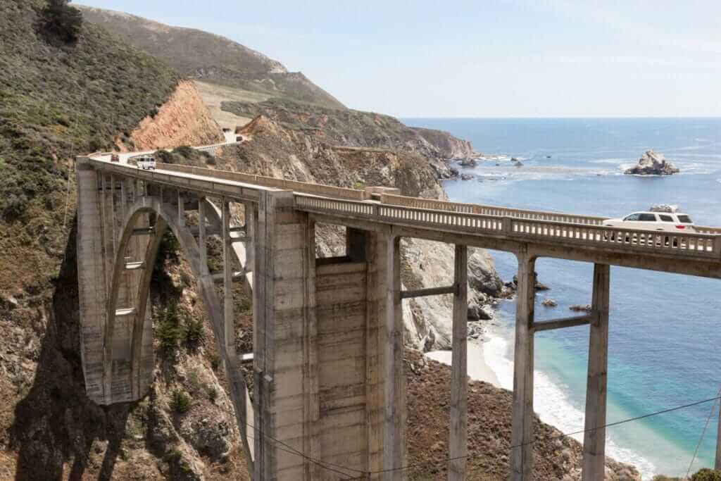 Bixby Creek Bridge with the ocean on one side and mountains on the other. Cars crossing the bridge.