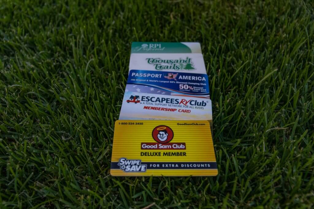 Pile of camping membership club cards, including Good Sam laid out on the grass