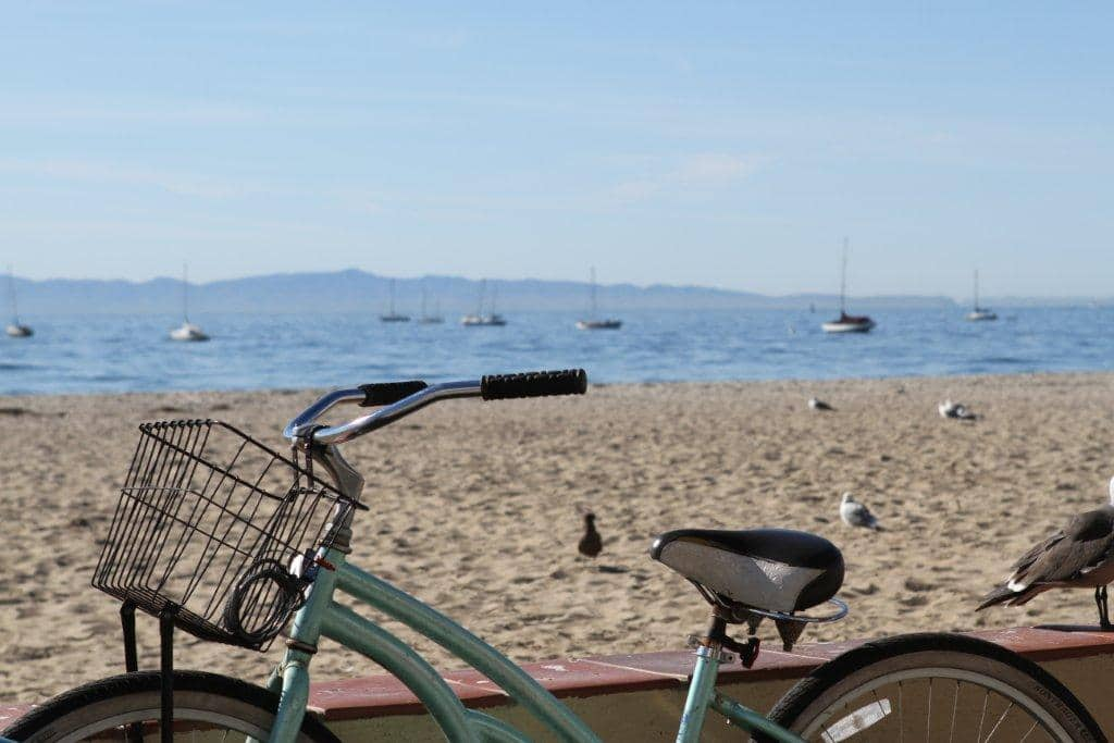 Bike leaning against a small wall with the beach and ocean in the background. Biking is one of the things to do in Santa Barbara.