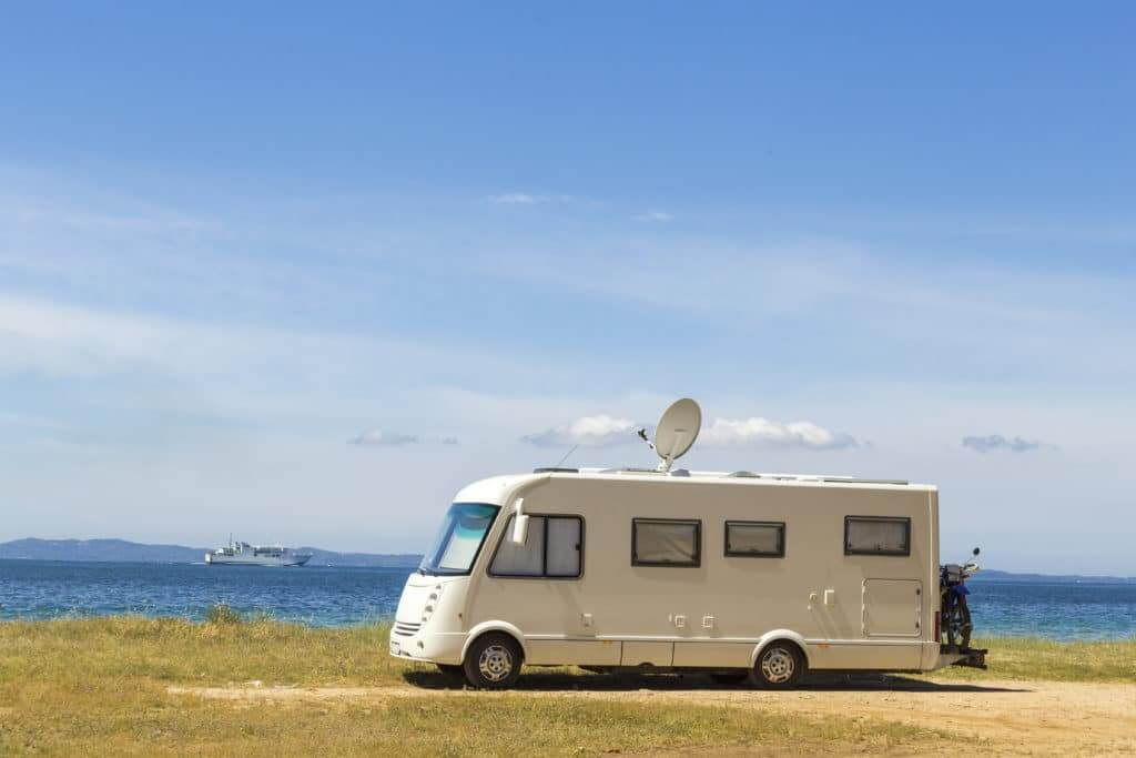 RV in a field of dried grass with water in the background and an RV antenna on the roof
