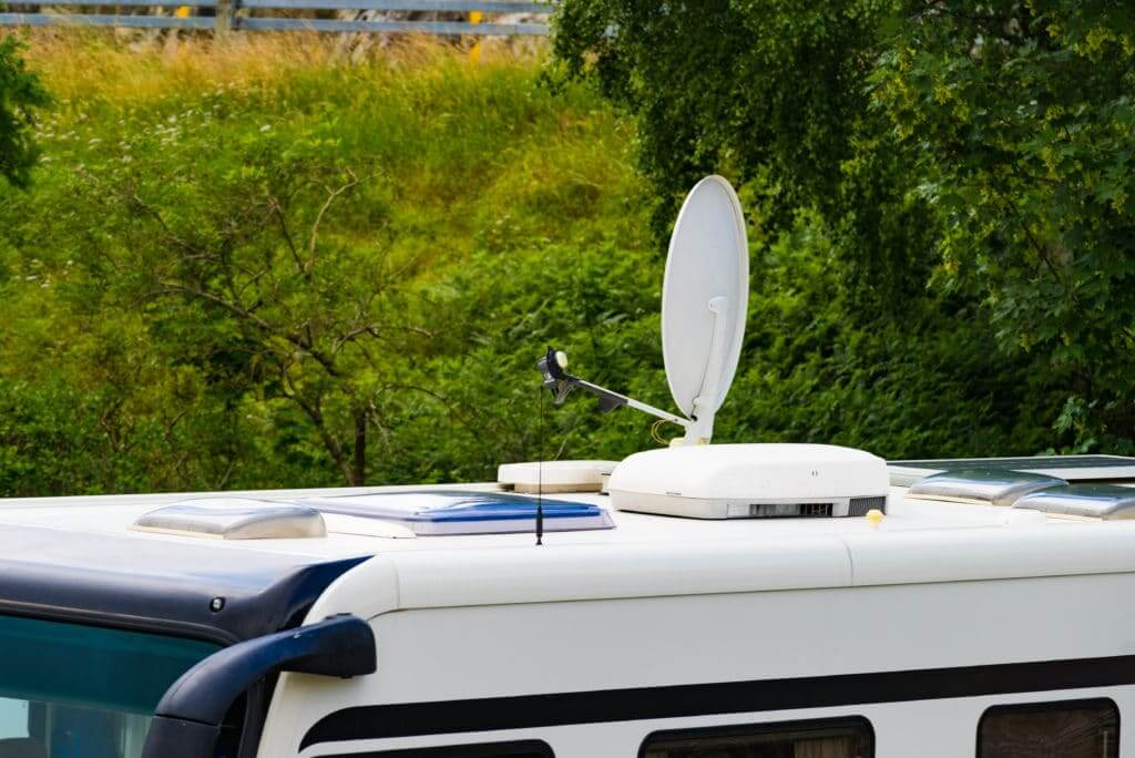 RV antenna on the roof of an RV with leaves in the background