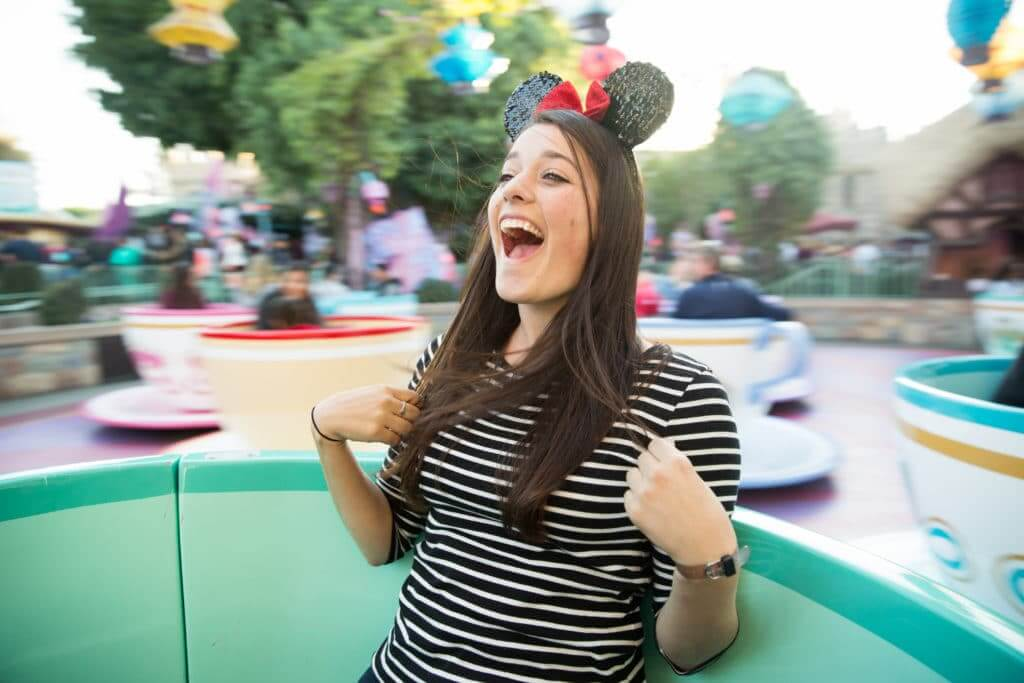 Save money on Disney tickets by purchasing half day tickets and have fun like this girl who is riding the teacups in the afternoon.