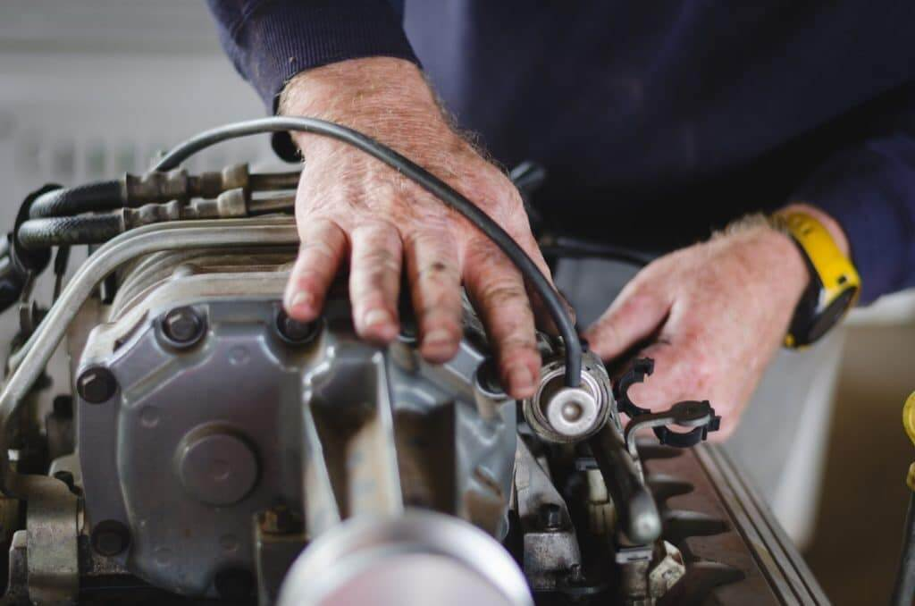 Mans hands on an engine, fixing a part. Know what you can modify on your engine so you don't void your RV warranty.