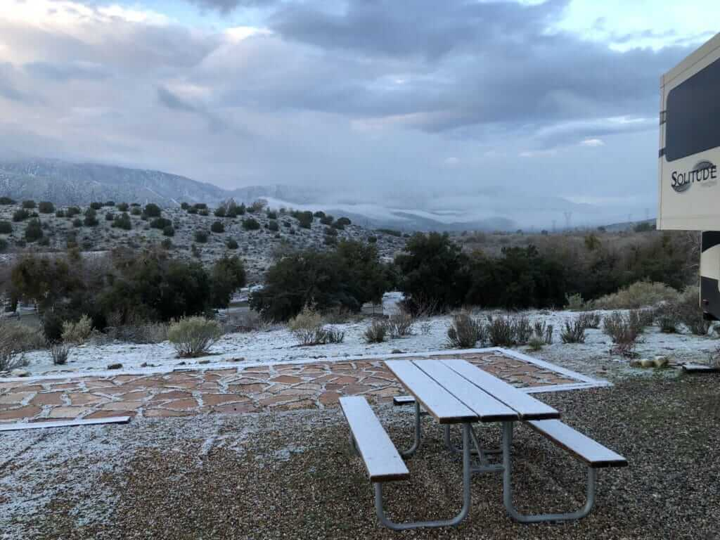 Brief layer of snow is shown on a campsite in Thousand Trails Soledad Canyon in Acton, CA
