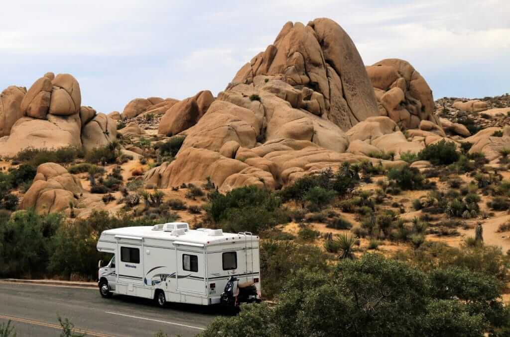 Class C RV small motorhome in front of large rocks