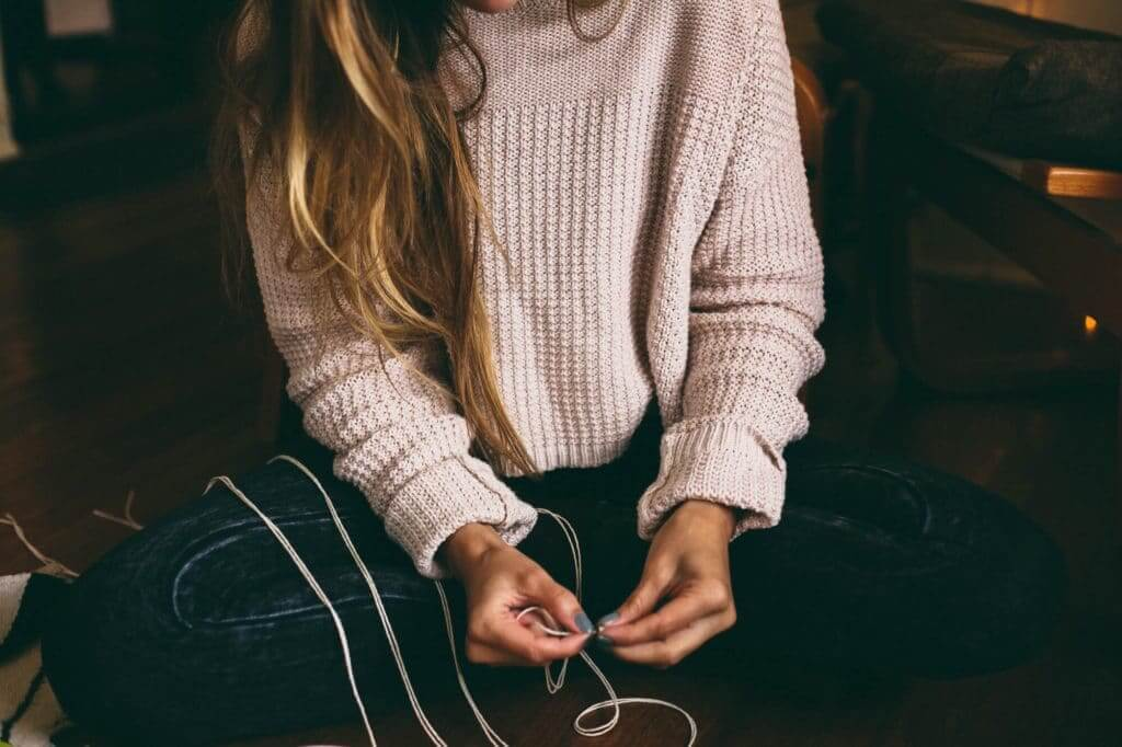 Woman in a bulky sweater holding string and making a gift by hand. Making gifts is one of the ways to save money.
