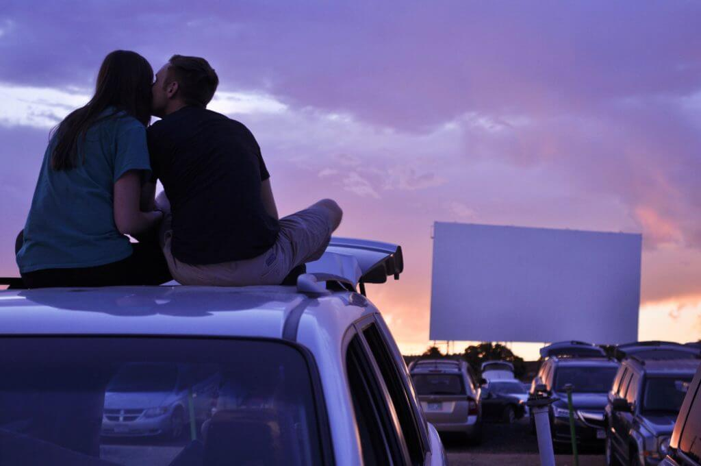 Couple sitting at sunset drive in movie theater